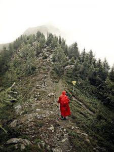 Mann mit Regencape auf einem Berg