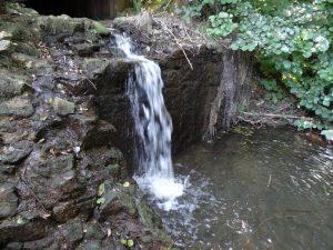 Ein kleiner Wasserfall liegt am Wegesrand.