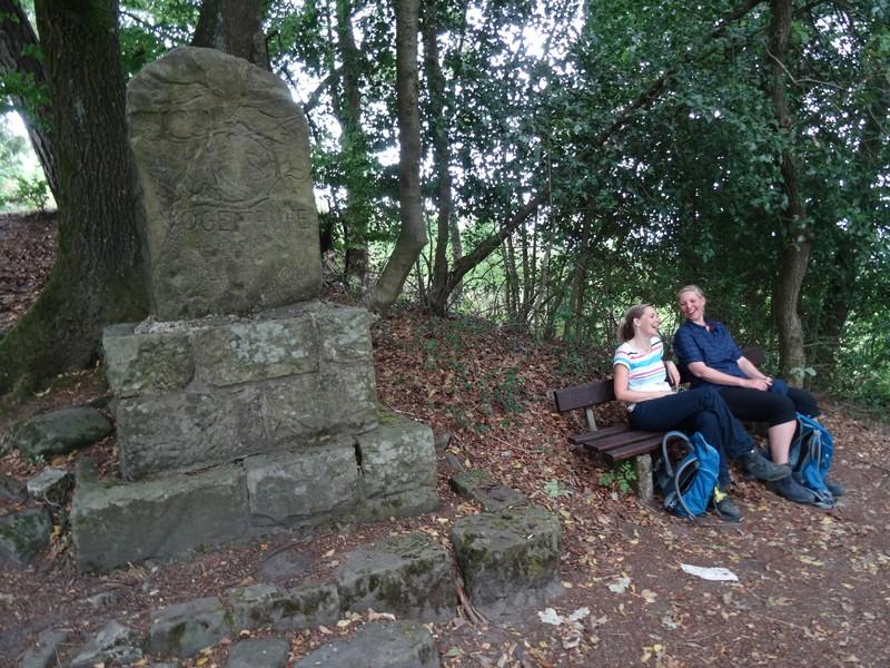 Zwei lachende Frauen mit Rucksäcken auf einer Bank neben einem Denkmal.