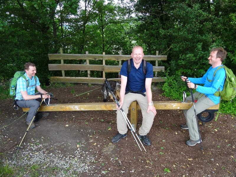 Drei Wanderer auf einer Wippe am Wegesrand