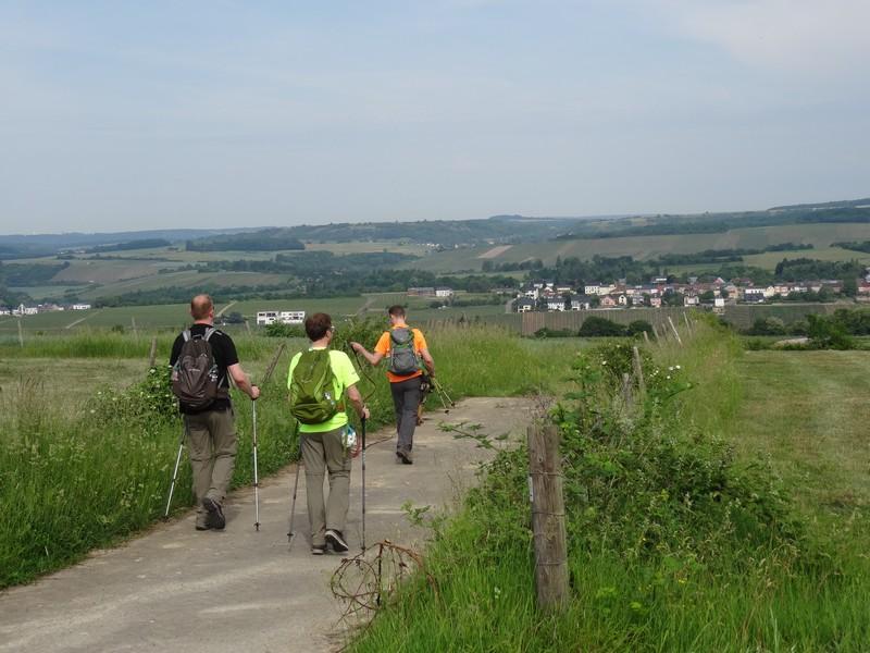 Drei Wanderer auf einem Weg, in weiter Ferne ein Ort,.