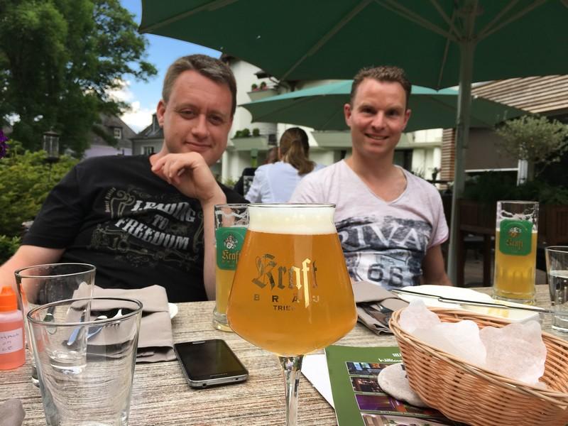 Zwei Wanderer im Biergarten, im Vordergrund ein Bier.