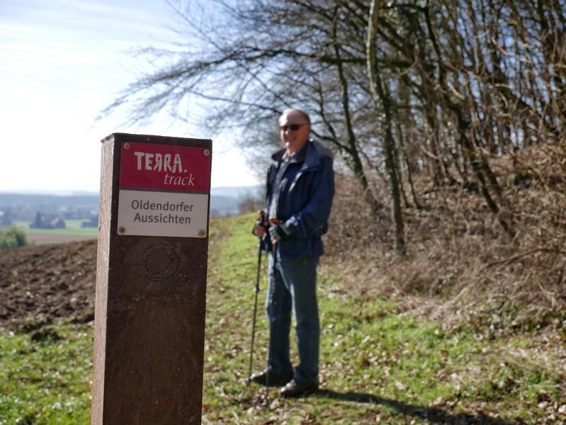 Wegweiser TERRA.track Oldendorfer Aussichten im Vordergrund, im Hintergrund unscharf ein Wanderer