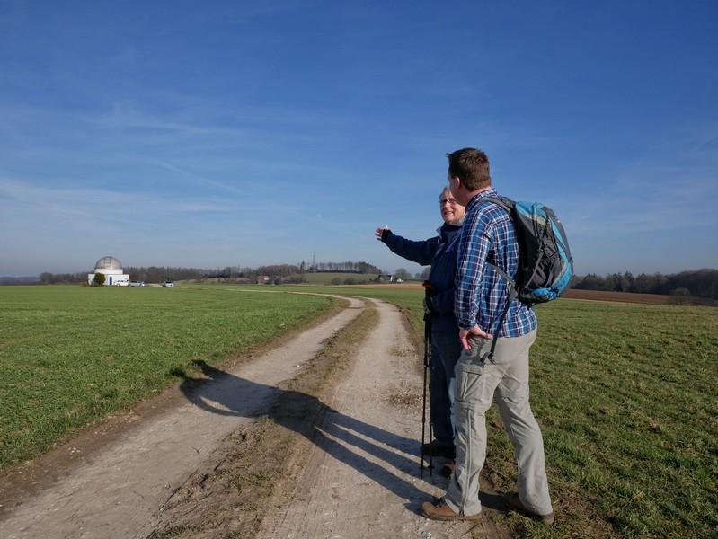Zwei Wanderer im Vordergrund, im Hintergrund die Sternwarte Melle.