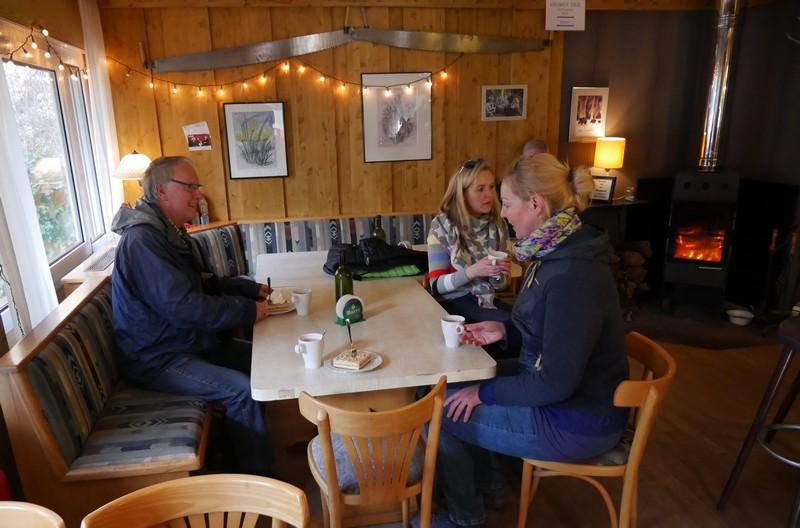 Blick in die Hütte: Drei Wanderer am Tisch, im Hintergrund der prasselnde Ofen