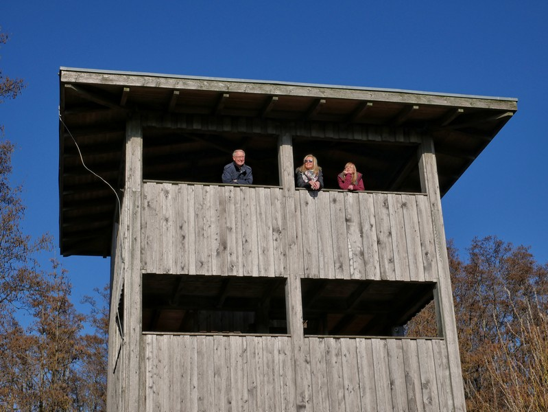 Aussichtsturm mit drei Wanderern, die von oben herab blicken