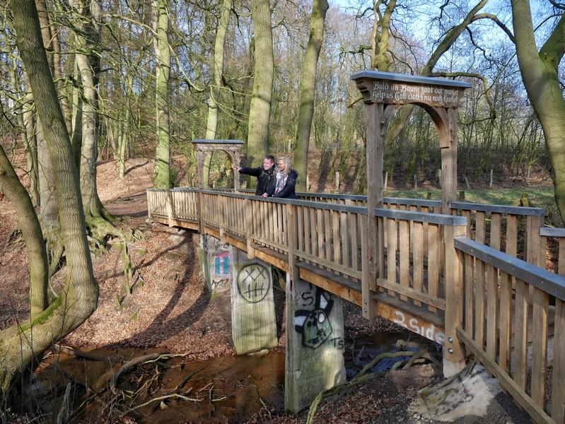 Brücke auf dem Weg zum Kloster, darauf zwei Wanderer