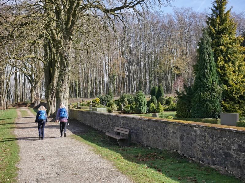 Wanderweg TERRA.track Holter Berg mit zwei Wanderern und zur Rechten der Holter Friedhof
