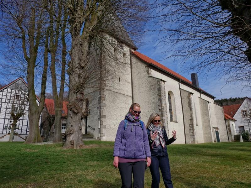 Kirche St. Urban im Hintergrund, im Vordergrund zwei Wanderer