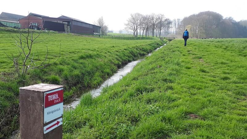 Das Bild zeigt im Vordergrund das Schild des TERRA.track Königsbrück, im Hintergrund Meike und den Bauernhof. Links ist ein kleiner Bach zu sehen.