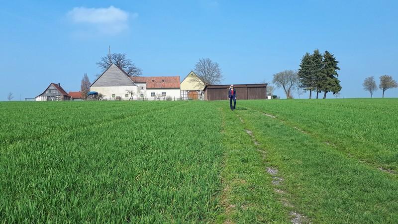 Das Bild zeigt Meike auf einem Wiesenweg, im Hintergrund ist ein Bauernhof zu sehen.
