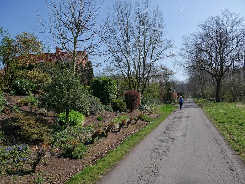 Meike wandert auf der Straße Am Sunderbach, links Häuser, rechts eine Wiese