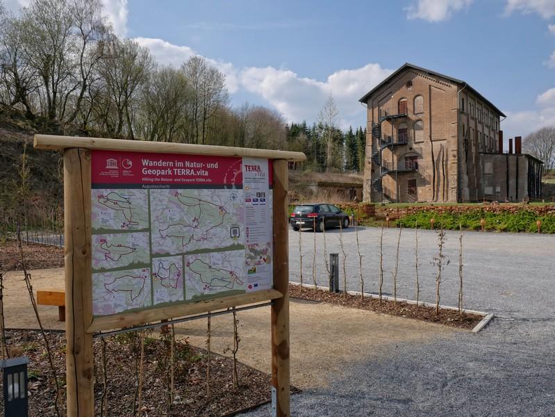 Wanderparkplatz mit Info-Tafel im Vordergrund und der Gedenkstätte Augustaschacht im Hintergrund.