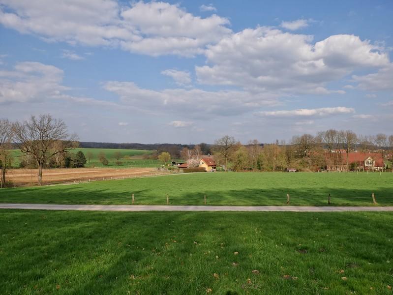 Das Bild zeigt die Aussicht vom TERRA.track Schau ins Land. Im Vordergrund sind Wiesen zu sehen, dahinter einige Häuser und Hügel.
