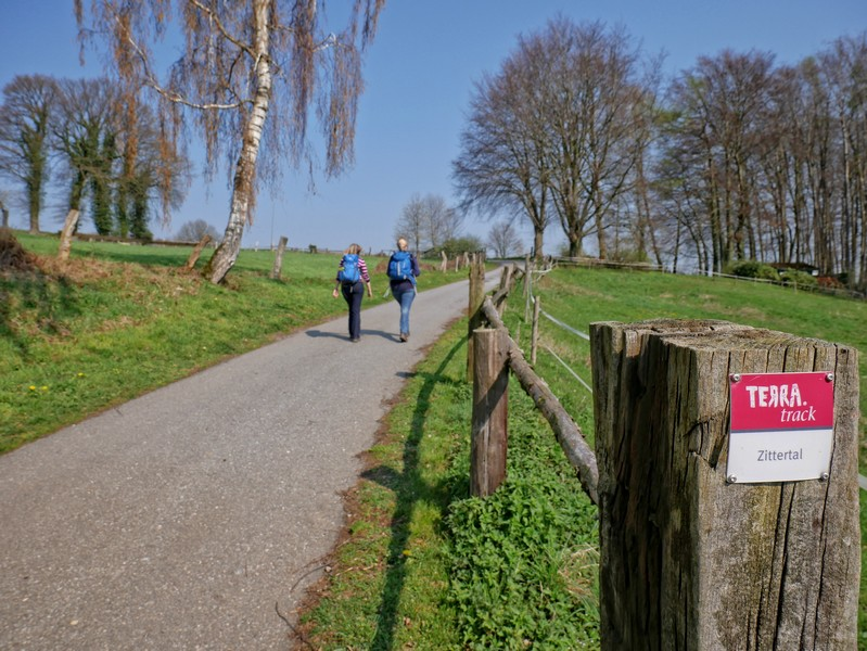 Das Bild zeigt im Vordergrund das Wegeschild Terra track Zittertal und im Hintergrund Meike und Svenja, die auf der kleinen Straße wandern.