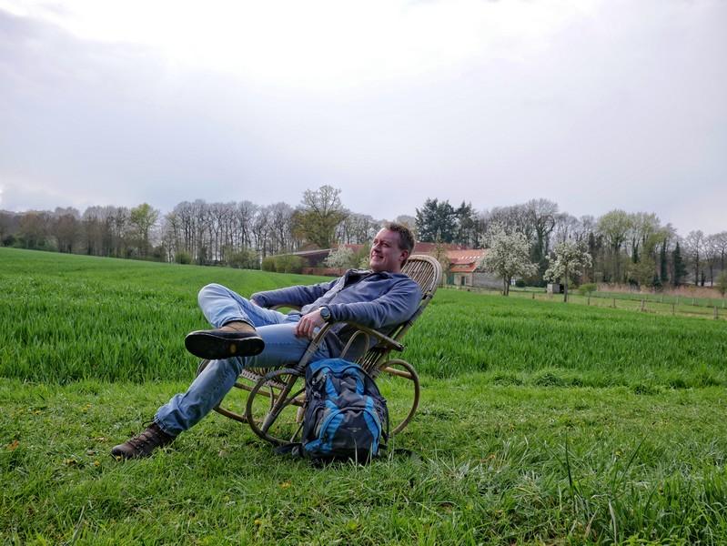 Das Bild zeigt den Wandervogel auf dem Schaukelstuhl vor dem Feld und im Hintergrund den Bauernhof, der zu Varus Deele gehört.