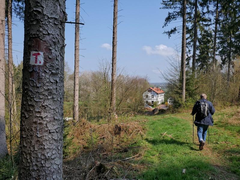 Das Bild zeigt einen Wanderer auf dem TERRA.track Hüggelrundweg, im Hintergrund ist ein Fachwerkhaus zu sehen.