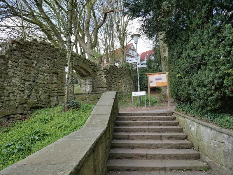 Das Bild zeigt Stufen, die vorbei führen an Mauerresten der Burg Tecklenburg. Im Hintergrund ist die Jugendherberge Tecklenburg zu sehen.