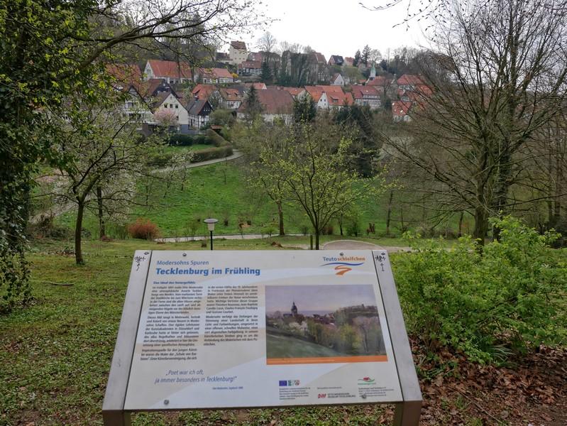 Das Bild zeigt eine Schautafel mit einem Werk Modersohns und im Hintergrund den Blick auf Tecklenburg, wie Modersohn ihn sah.