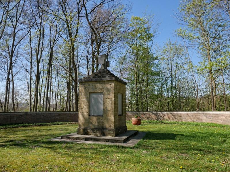 Das Bild zeigt die zentrale Stele des Ehrenmals, die von einer ringförmigen Ziegelmauer umgeben ist.