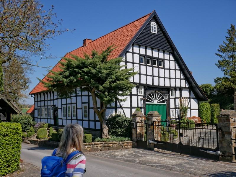 Das Bild zeigt Meike vor einem schmucken Fachwerkhaus in direkter Nachbarschaft des Renkenörener Sees.