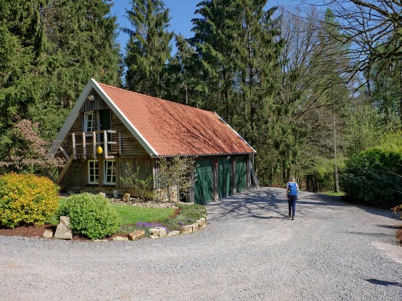 Das Bild zeigt ein kleineres Holzhaus und danebn Meike auf dem TERRA.track Borgloher Schweiz.