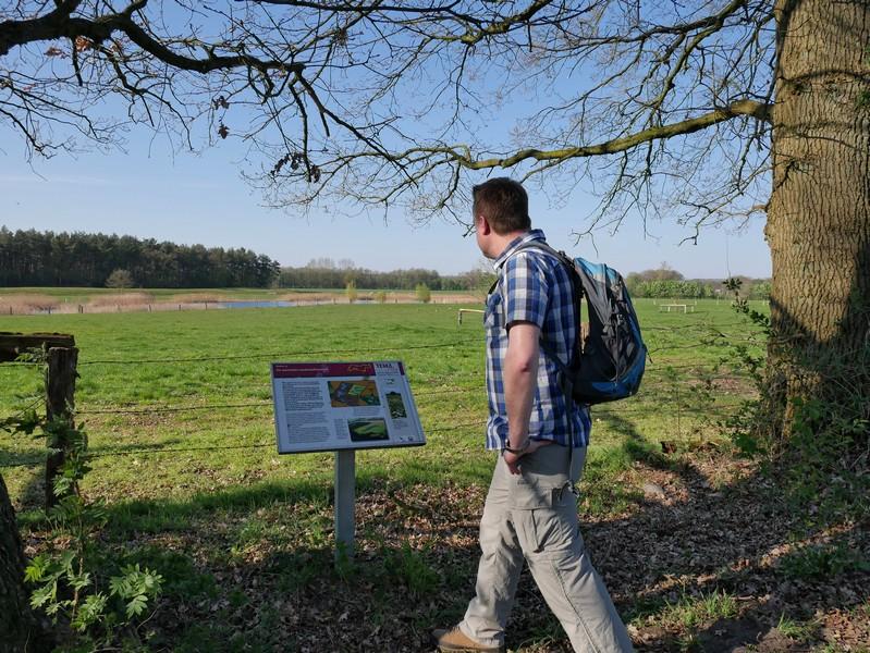 Das Bild zeigt den Wandervogel vor einer Info-Tafel. Im Hintergrund ist ein kleiner See inmitten einer grünen Weide zu sehen.