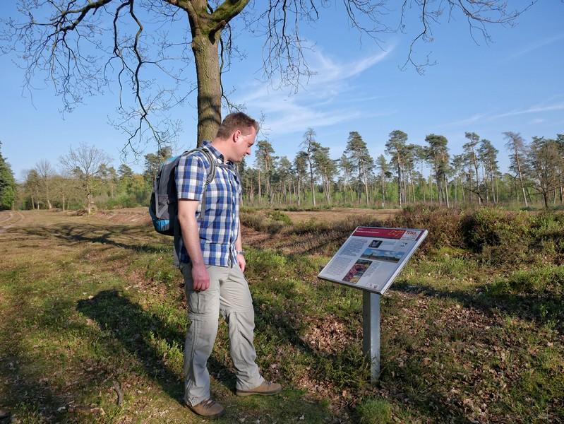 Das Bild zeigt den Wandervogel neben einem Info-Schild zu der Heidelandschaft, die im Hintergrund ebenfalls zu sehen ist.
