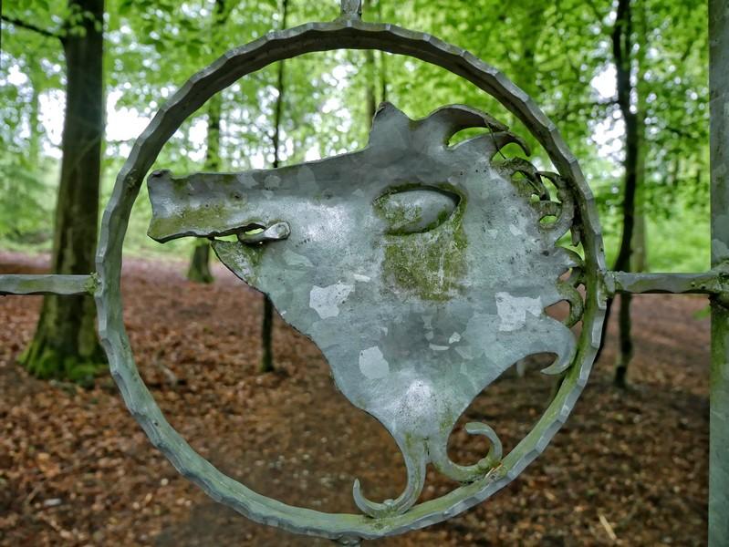 Das Bild zeigt ein Wildschweinsymbol im Gatter des Tores zum Wildpark Melle.