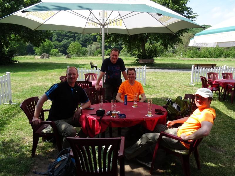 Das Bild zeigt die vier Wanderer im Schatten eines Sonnenschirms im Biergarten.