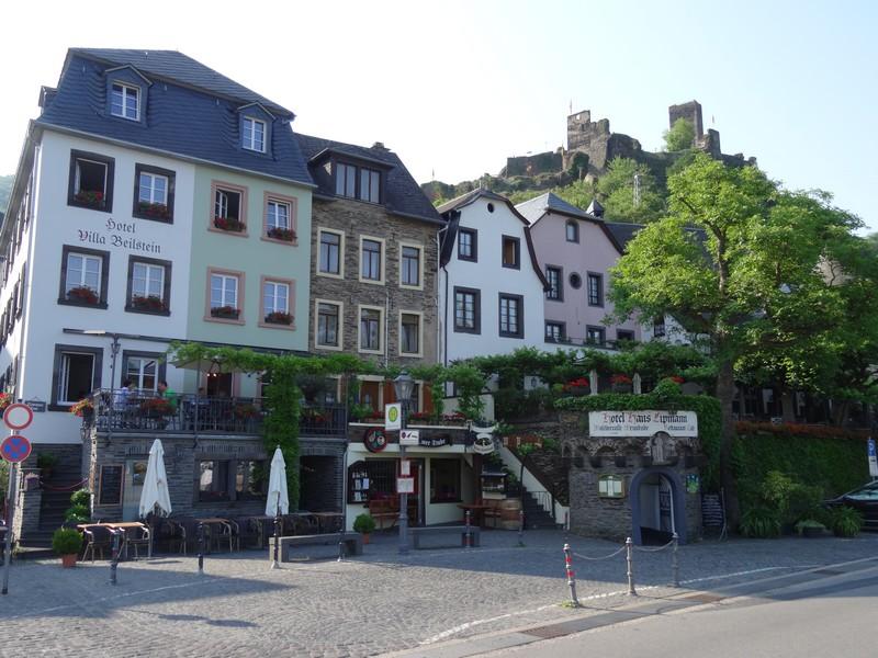 Das Bild zeigt die Häuser Beilsteins am Moselufer. Im Hintergrund ist die Burgruine zu sehen.