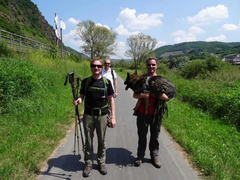 Das Bild zeigt drei Wanderer, einer trägt eine Schäferhündin.