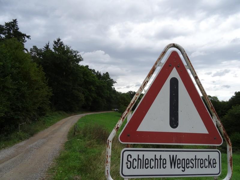 """Das Bild zeigt ein Schild mit der Aufschrift """"Schlechte Wegstrecke""""."""