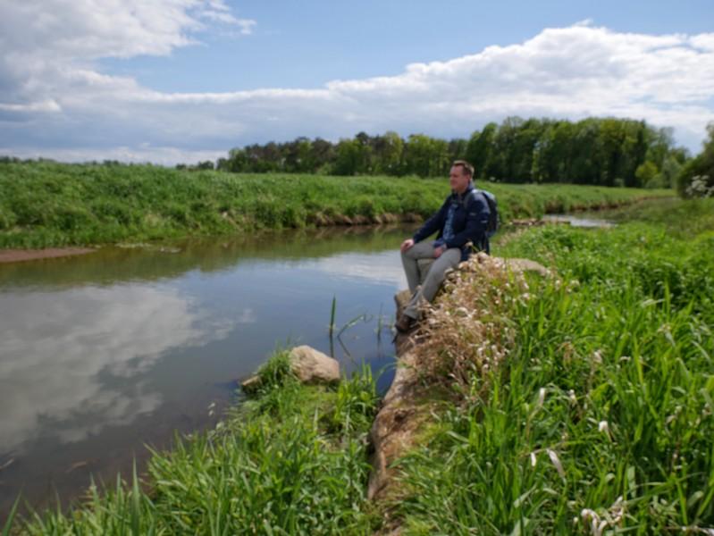 Das Bild zeigt im Hintergrund den sitzenden Wandervogel auf einem Stein und links die Bever.