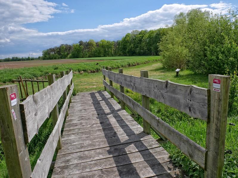 Das Bild zeigt eine hölzerne Brücke, zu beiden Seiten sind die Wegweiser des TERRA.track Dinkel und Emmer angebracht.