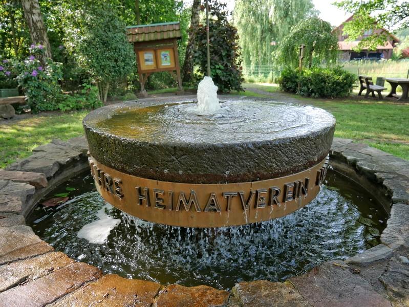 Das Bild zeigt den Brunnen auf dem Dorfplatz in Ueffeln.