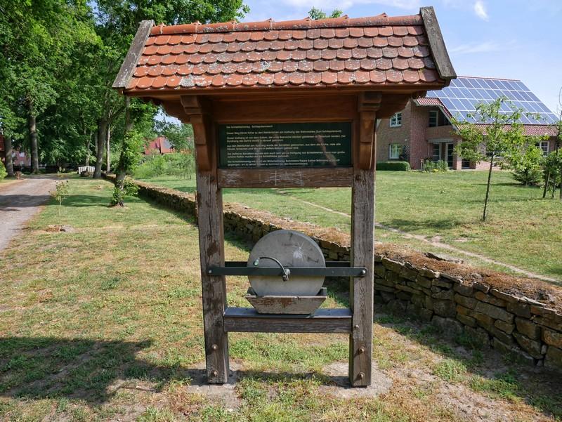 Das Bild zeigt eine Info-Tafel am Wegesrand mit einem Schleifstein.