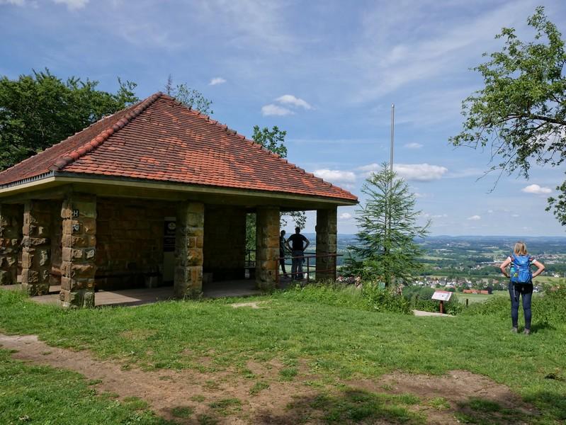Das Bild zeigt links die Hütte der Schwedenschanze und rechts Meike, die die Aussicht genießt.