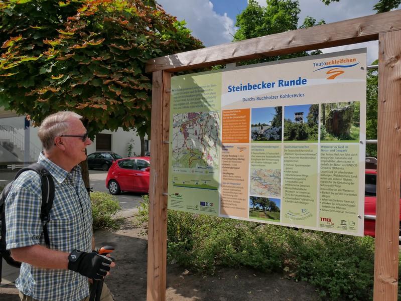 Das Bild zeigt einen Wanderer vor der Info-Tafel zum Teutoschleifchen Steinbecker Runde.