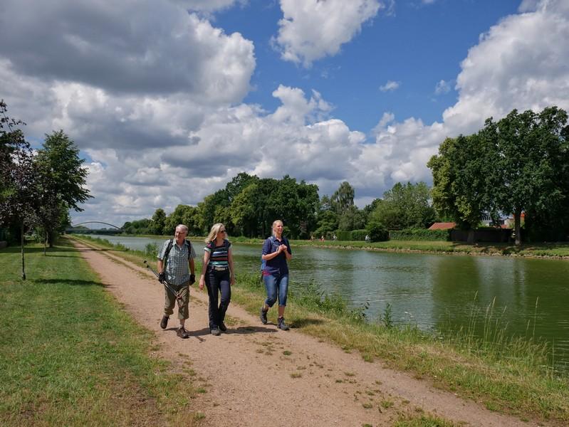 Das Bild zeigt drei Wanderer am Mittellandkanal auf dem Teutoschleifchen Steinbecker Runde.