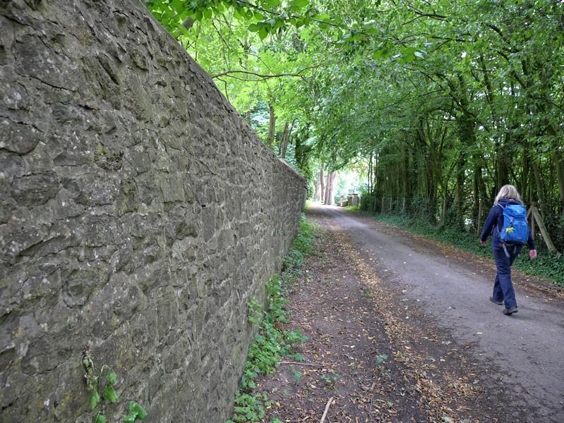 Das Bild zeigt Meike auf dem Wanderweg, der links von einer sehr hohen Steinmauer begleitet wird.