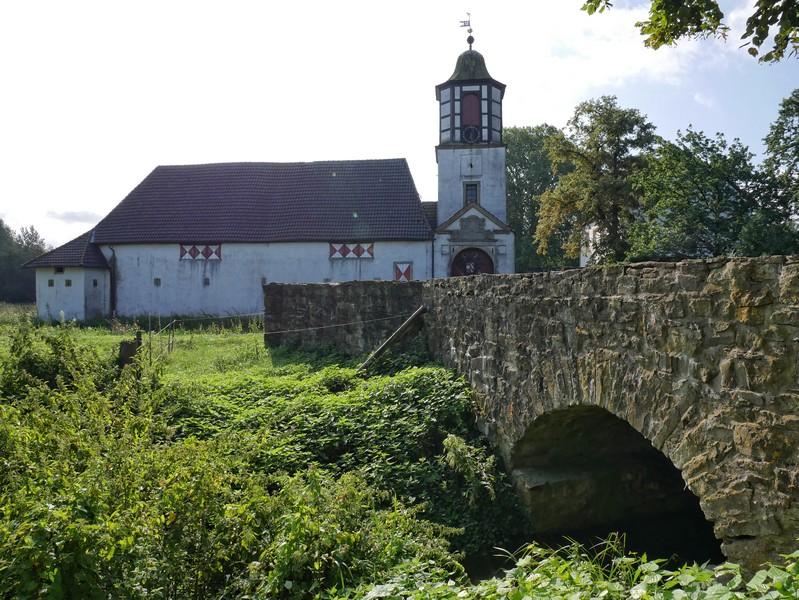 Das Bild zeigt Schloss Alt Barenaue, im Vordergrund die steinerne Brücke.