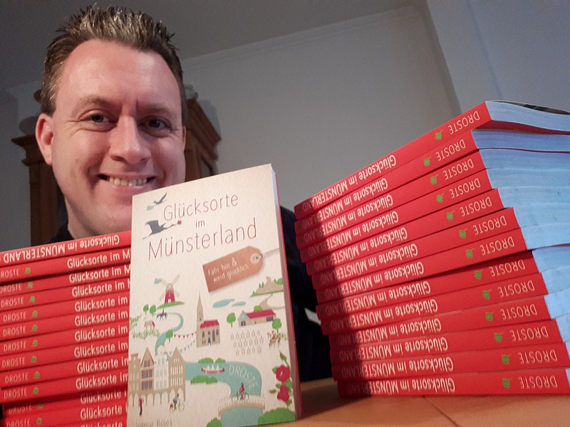 Das Bild zeigt den Autor mit mehreren Büchern.